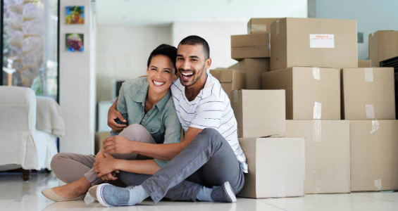A man and woman sitting happily next to moving boxes
