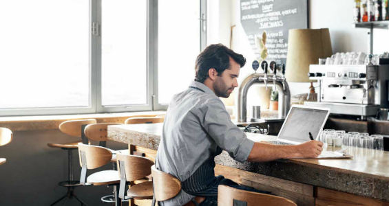 Business owner sitting at counter with laptop