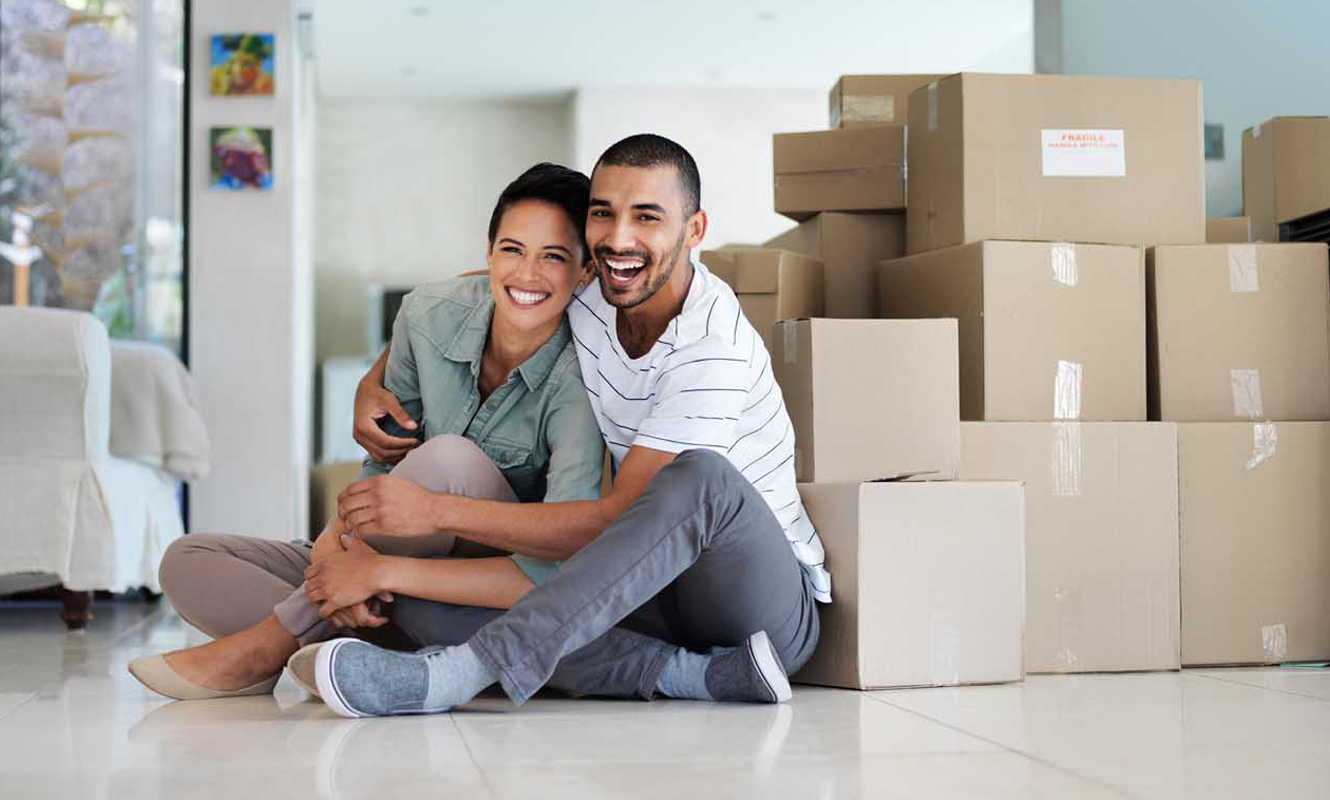Happy man and woman next to moving boxes